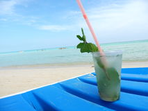Drink on a Sandy Beach. Cuban Rum Classic Mojito on the beach chair overlooking clear blue turquoise waters stock photo