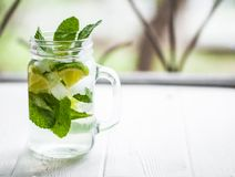 Mojito cocktail in glass jars on a window sill. Copy space royalty free stock images