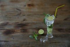 Mojito-Cocktail im Glas mit Eis, Minze und grünem Kalk auf einem hölzernen rustikalen Hintergrund Mit Kopienraum f?r Text nahaufn lizenzfreie stockfotos