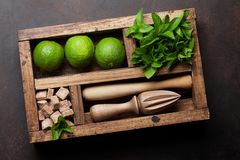 Mojito cocktail ingredients box. Mojito cocktail ingredients and bar accessories box on wooden table. Top view Stock Photos