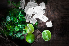 Mojito cocktail Ingredients - Fresh mint, limes, ice over wooden. Backdrop. Top view, copy space Stock Image