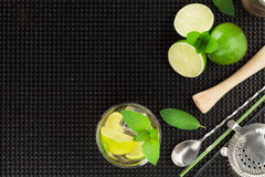 Mojito cocktail and ingredients over black rubber mat Royalty Free Stock Images