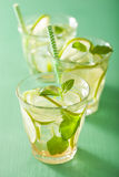 Mojito cocktail and ingredients over green background Stock Photography