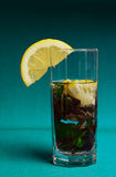 Mojito cocktail with lemon and mint on blue background Royalty Free Stock Image