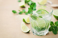 Mojito cocktail with lime, ice and mint leaves on wooden table, summer drink Royalty Free Stock Photos