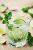 Mojito cocktail with lime, ice and mint leaves on wooden table, summer drink Stock Images