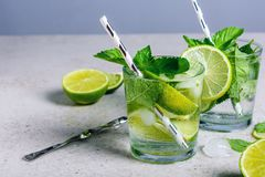 Mojito cocktail. With lime and mint in glass on a grey stone background royalty free stock photo