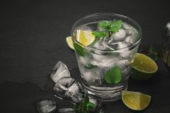 Mojito cocktail with lime and mint in glass on a grey stone back Stock Image