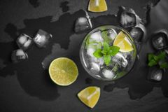 Mojito cocktail with lime and mint in glass on a grey stone back Royalty Free Stock Photography