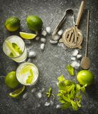 Mojito cocktail with lime and mint in glass and bar tools on a stone table. royalty free stock photography