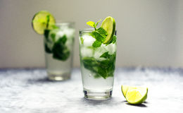 Mojito cocktail with lime and mint in glass on a white background Royalty Free Stock Photography