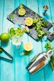 Mojito cocktail with lime and mint in highball glass on a blue wood table. Drink making tools and ingredients for cocktail.  stock images