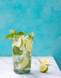 Mojito cocktail with lime and mint in highball glass on a marble table Blue background Copy space Royalty Free Stock Images