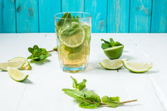 Mojito cocktail with lime and mint in highball glass on a wood table. Blue background Stock Photography