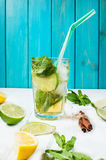 Mojito cocktail with lime and mint in highball glass on a wood table. Blue background Stock Photo