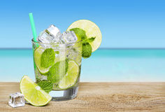 Mojito cocktail with lime over beach background Royalty Free Stock Photo