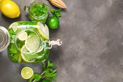 Mojito cocktail in mason jar with garnish on black table. Top view. Copy space for text royalty free stock photos