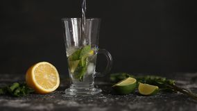 Mojito cocktail with mint and lime on black background stock video footage