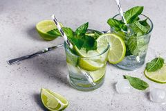 Mojito cocktail. With lime and mint in glass on a grey stone background royalty free stock image