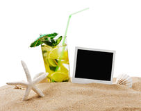Mojito cocktail on the sandy beach with blurred sea Stock Images