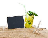 Mojito cocktail on the sandy beach with blurred sea Royalty Free Stock Image