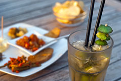 Mojito cocktail with snacks on wooden table Royalty Free Stock Photography