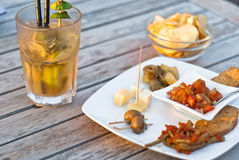 Mojito cocktail with snacks on wooden table Royalty Free Stock Photo