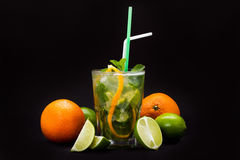 Mojito cocktail with straws and fruit on a black background Royalty Free Stock Images
