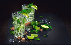 Mojito cocktail on a table. Summer cocktail with rum, lime, mint, ice cubes and brown sugar royalty free stock image