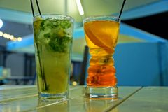 Mojito and cocktail in two long glass glasses on the table stock images