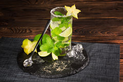 Mojito cocktail on a wooden background. Fresh lime, mint leaves and ice cubes in a transparent glass. Refreshing alcohol drink. Stock Photos
