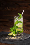 Mojito cocktail on a wooden background. Fresh lime mojito with a straw, mint leaves and ice cubes. Refreshing alcohol. Copy space. royalty free stock photo