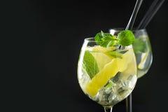 Mojito coctail eller lemonad med limefrukt och mintkaramellen i exponeringsglas på den svarta tabellen close upp f?r citrus vatte royaltyfri bild