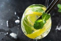 Mojito coctail eller lemonad med limefrukt och mintkaramellen i exponeringsglas p? den svarta tabellen close upp f?r citrus vatte royaltyfri fotografi