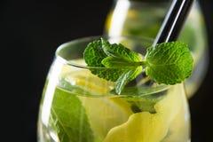 Mojito coctail eller lemonad med limefrukt och mintkaramellen i exponeringsglas p? den svarta tabellen close upp f?r citrus vatte royaltyfria foton