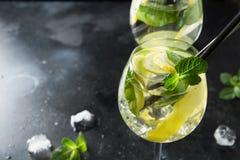 Mojito coctail eller lemonad med limefrukt och mintkaramellen i exponeringsglas p? den svarta tabellen close upp f?r citrus vatte royaltyfria bilder