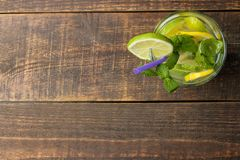 Mojito coctail i ett exponeringsglasexponeringsglas med limefrukt, mintkaramellen och citronen på en träbrun tabell Top beskådar royaltyfri foto