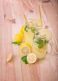 Mojito coctail med grön limefrukt och ljusa gula citroner med smakliga sidor av mintkaramellen med gula sugrör på en ljus tabellb Arkivfoton
