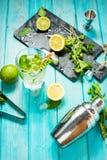 Mojito coctail med limefrukt och mintkaramellen i highballexponeringsglas på en blå wood tabell Drinkdanandehjälpmedel och ingred arkivbilder