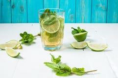 Mojito coctail med limefrukt och mintkaramellen i highballexponeringsglas på en wood tabell background card congratulation invita Arkivbild