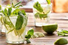 Mojito coctail med rom, limefrukt och sodavatten som garneras med mintkaramellen Royaltyfri Bild