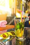 Mojito coctail och stilfull gul solglasögon på tabellen i den ljusa soliga dagen för utomhus- kafé arkivbilder