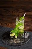 Mojito coctail på en träbakgrund Ny limefruktmojito med ett sugrör, mintkaramellsidor och iskuber Uppfriskande alkohol kopiera av Royaltyfri Bild