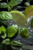 Mojito coctaildrink med limefrukt, is och mintkaramellen royaltyfria foton