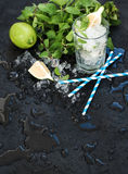 Mojito cooking set. Bunch of fresh mint, lime, chipped ice and coctail glass over black slate stone backdrop Stock Image