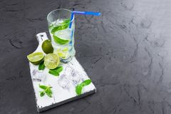 Mojito en verres, à côté de chaux et de menthe sur la planche à découper Copiez l'espace photographie stock