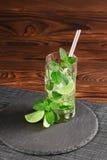 Mojito freddo con ghiaccio e calce Mojito verde con rum o liquore su un fondo di legno Bevande alcoliche di rinfresco Copi lo spa Immagini Stock