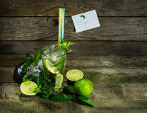 Mojito with ice on wooden background. Glass with Mojito and crushed ice on wooden background royalty free stock image