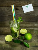 Mojito with ice on wooden background. Glass with Mojito and crushed ice on wooden background royalty free stock photography