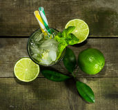 Mojito with ice on wooden background. Glass with Mojito and crushed ice on wooden background royalty free stock images